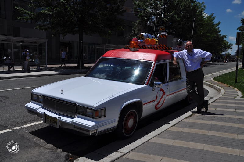 "A fan stands next to the new Ecto-1 from the upcoming film ""Ghostbusters"" outside of the Clarendon Metro"